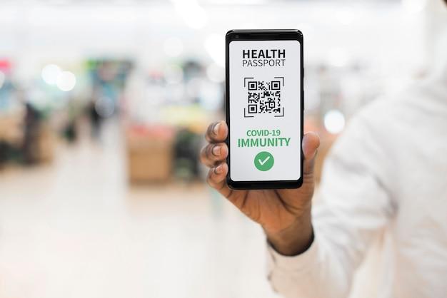 スマートフォンで仮想健康パスポートを持っている人の正面図