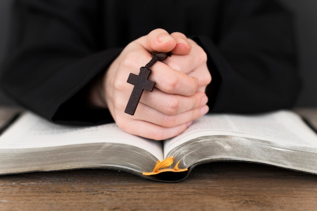 십자가와 거룩한 책으로기도하는 사람의 전면보기
