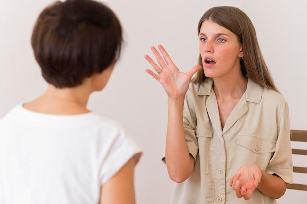 Вид спереди человека, обучающего женщину языку жестов