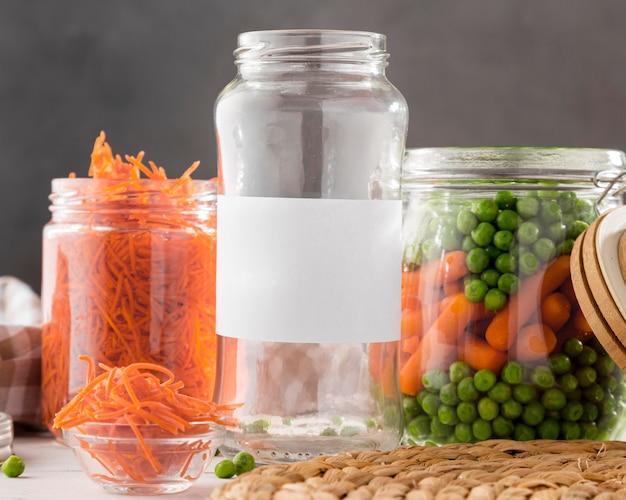 Вид спереди маринованного гороха и молодой моркови в прозрачных стеклянных банках