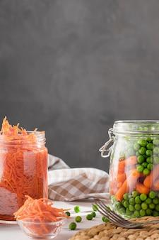 Вид спереди маринованного гороха и молодой моркови в прозрачных банках с копией пространства