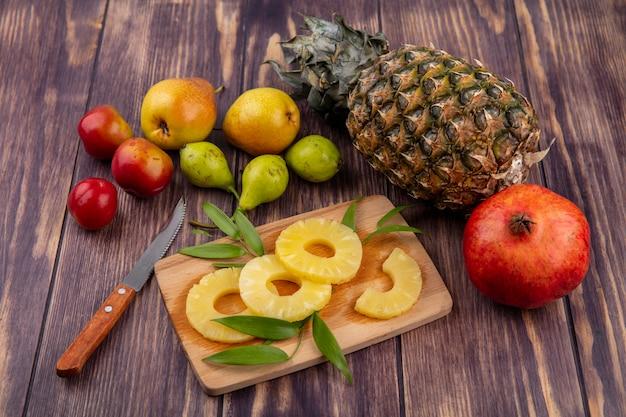 Вид спереди ломтики ананаса на разделочную доску и ананас гранатовый персик слива с ножом на зеленой поверхности