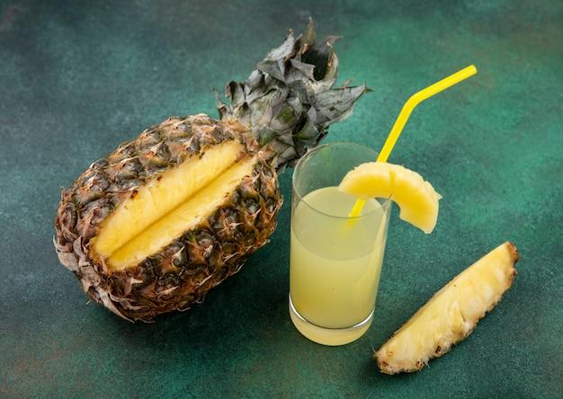 Вид спереди ананаса с одним куском, вырезанным из цельного фруктового и ананасового сока на зеленой поверхности