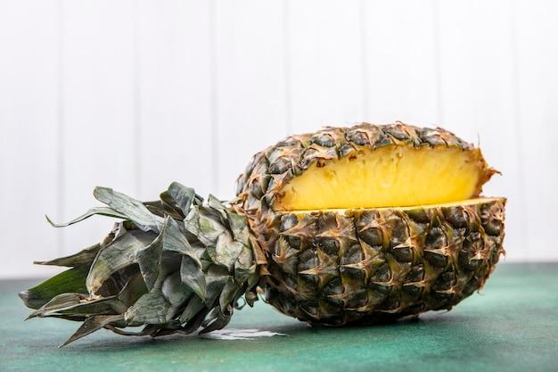 緑の表面と白い表面のフルーツ全体から切り取られたワンピースのパイナップルの正面図