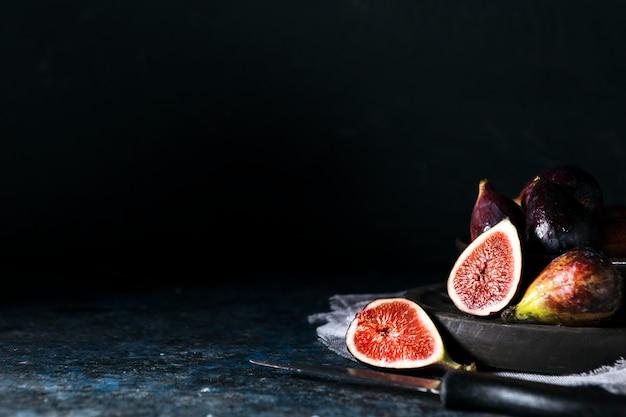 Вид спереди тарелки с гроздью осеннего инжира и копией пространства