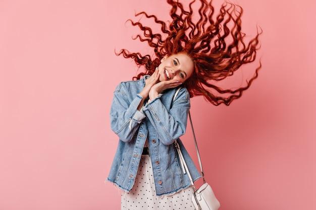 Вид спереди довольной имбирной девушки в повседневной одежде. студия выстрел рыжеволосой женщины в джинсовой куртке, танцы на розовом фоне.