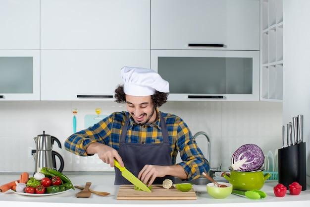 新鮮な野菜とキッチンツールで調理し、白いキッチンでピーマンを刻んでポジティブな男性シェフの正面図