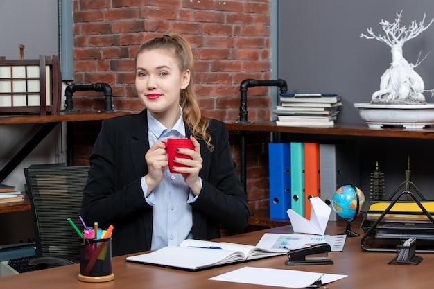 테이블에 앉아 사무실에 빨간 컵을 들고 긍정적인 젊은 여성의 전면 보기