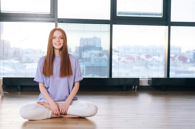 明るい事務室の窓の背景に蓮のポーズで床に座って瞑想するポジティブな若い女性の正面図。