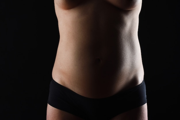 黒の背景に妊娠中の腹のnaketの正面図