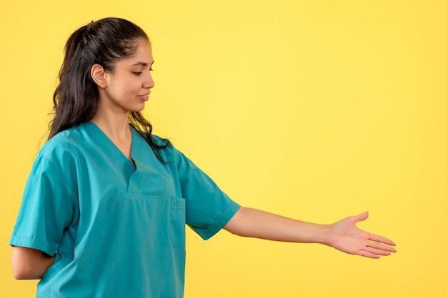 노란색 벽에 손을주는 예쁜 여성 의사의 전면보기