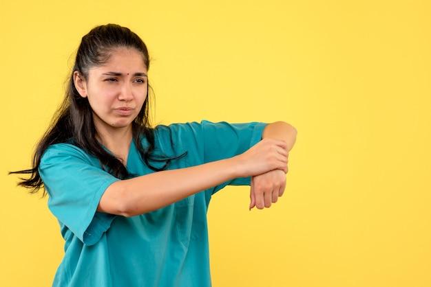 黄色い壁に痛みを伴う彼女の腕を保持しているきれいな女性医師の正面図