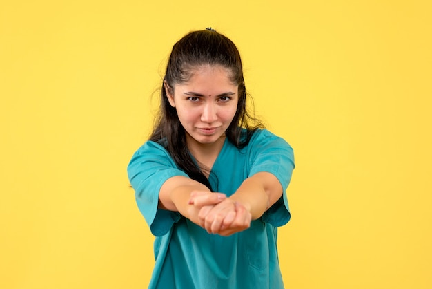 黄色の壁に手を一緒に保持しているきれいな女性医師の正面図