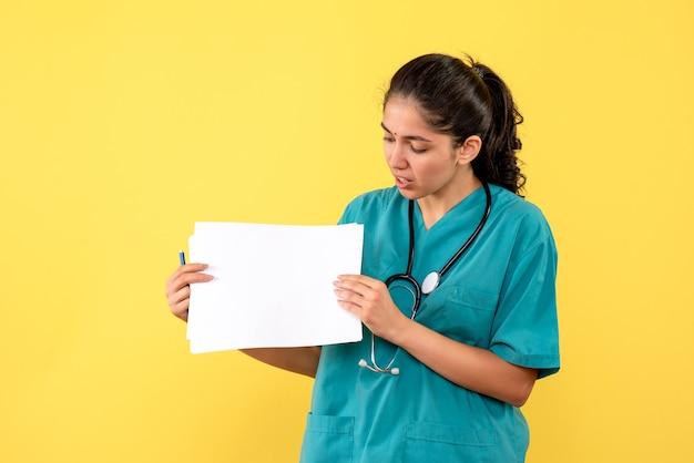 노란색 벽에 서있는 서류를 들고 제복을 입은 예쁜 여성 의사의 전면보기