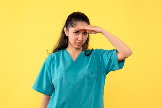 黄色い壁に何かを見ているきれいな女性医師の正面図