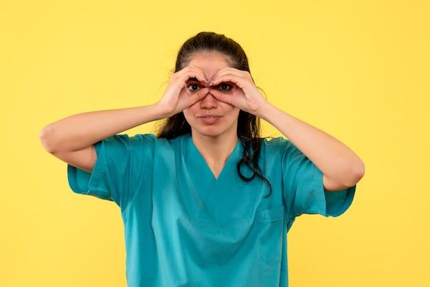 黄色の壁に双眼鏡を作っているきれいな女性医師の正面図