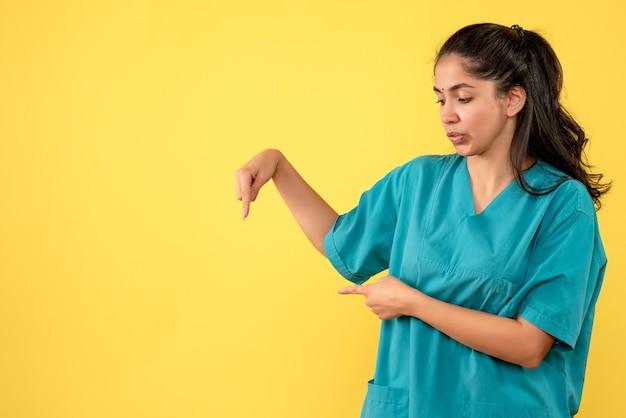 壁を指しているきれいな女性医師の正面図。黄色い壁に