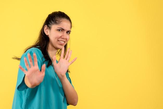 노란색 벽에 뭔가를 막으려 고 예쁜 여성 의사의 전면보기
