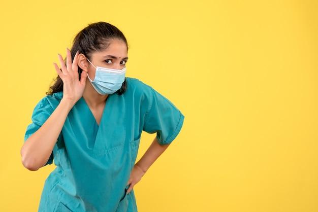 노란색 벽에 뭔가 듣고 의료 마스크와 예쁜 여성 의사의 전면보기
