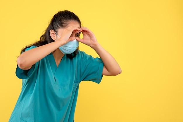 노란색 벽에 뭔가보고 의료 마스크와 예쁜 여성 의사의 전면보기