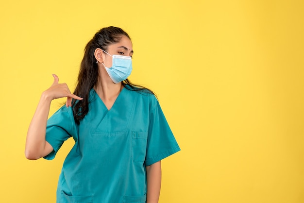 노란색 벽에 전화 제스처를 만드는 의료 마스크와 예쁜 여성 의사의 전면보기
