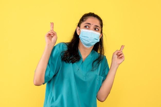 노란색 벽에 행운을 빌어 요 기호를 만드는 의료 마스크와 예쁜 여성 의사의 전면보기