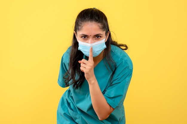 노란색 벽에 쉿 기호를 만드는 의료 마스크와 예쁜 여성 의사의 전면보기