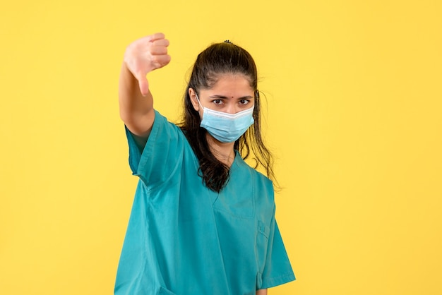 노란색 벽에 기호 아래로 엄지 손가락을 만드는 의료 마스크와 예쁜 여성 의사의 전면보기