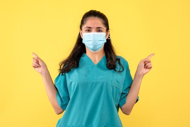 노란색 벽에 의료 마스크와 예쁜 여성 의사의 전면보기