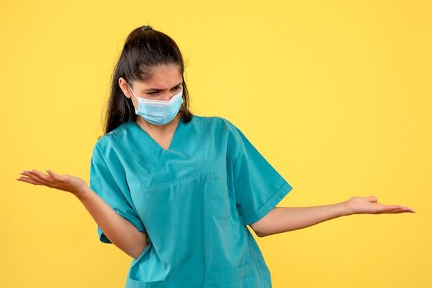 黄色の壁に手を開く医療マスクを持つきれいな女性医師の正面図