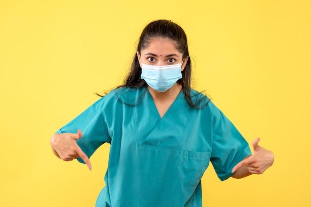 壁を指している医療マスクを持つきれいな女性医師の正面図。黄色い壁に