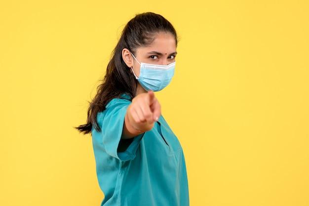 黄色の壁に指の正面を指している医療マスクを持つきれいな女性医師の正面図