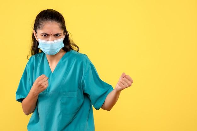黄色の壁にパンチを示す医療マスクを持つきれいな女性医師の正面図