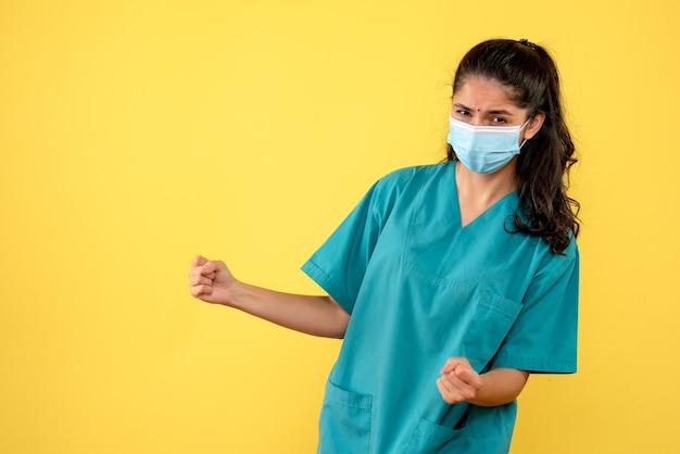 黄色の壁に勝利のジェスチャーを示す医療マスクを持つきれいな女性医師の正面図