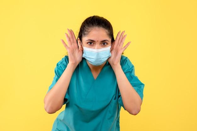 黄色の壁に立っている医療マスクを持つきれいな女性医師の正面図