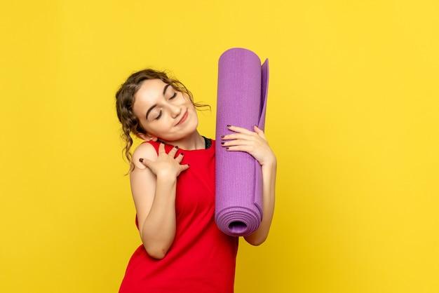 노란색에 보라색 카펫을 들고 예쁜 여성의 전면보기