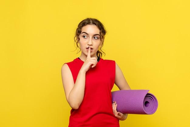 黄色の紫色のカーペットを保持しているきれいな女性の正面図