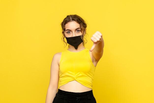 Вид спереди красивой женщины в черной маске на желтом