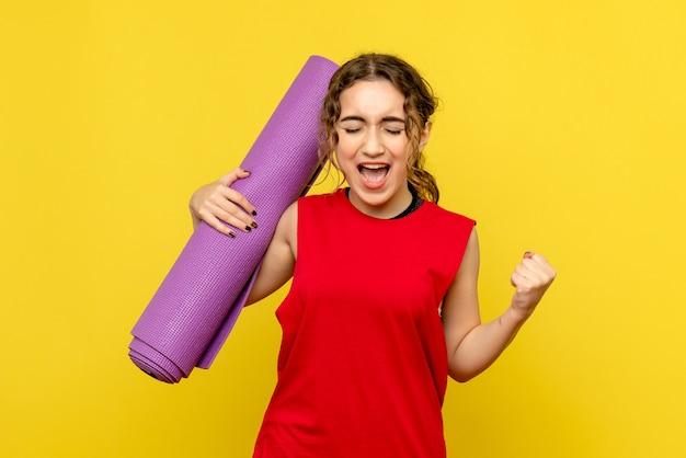 黄色の紫色のカーペットで喜んでいるきれいな女性の正面図