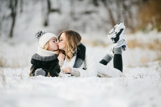 雪の上に横たわってキスをしているかわいい母親と彼女の小さなかわいい娘の正面図