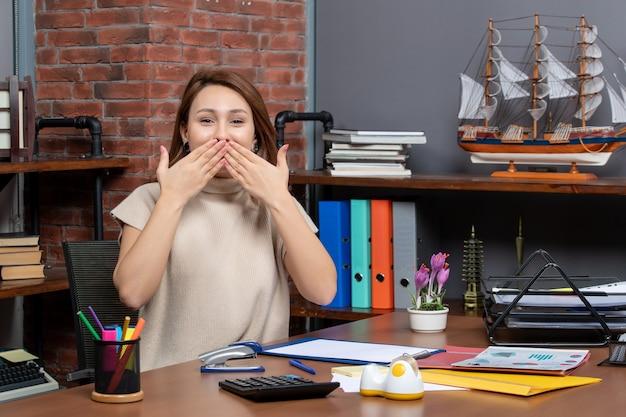 オフィスで働く手で彼女の口を覆うきれいな女性の正面図