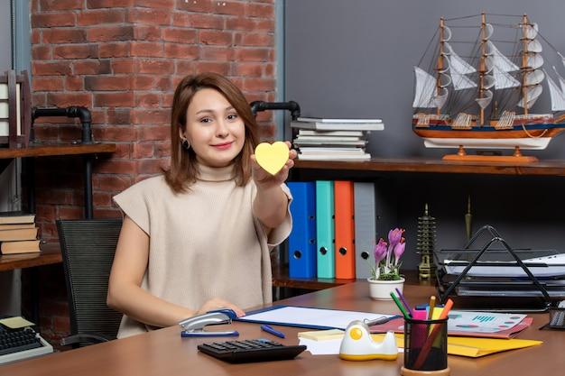 Вид спереди красивой женщины, держащей бумагу для заметок в форме сердца