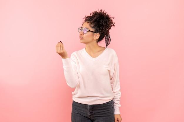 Вид спереди красивой женщины разговаривает с кем-то на розовой стене
