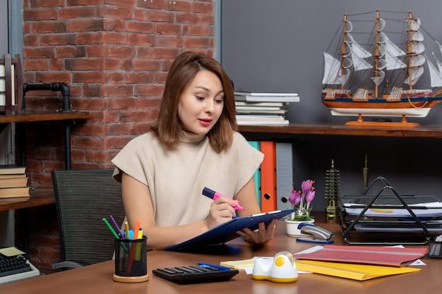 壁に座っている蛍光ペンを使用してきれいな女性の正面図