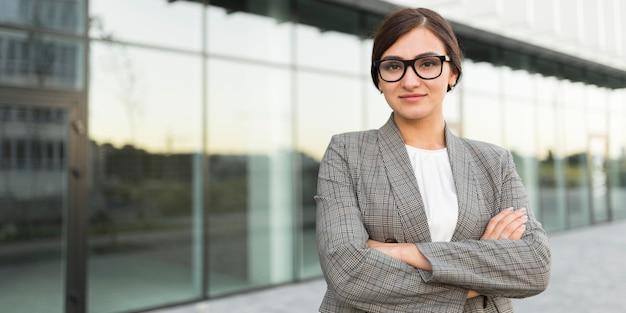Вид спереди профессиональной деловой женщины, позирующей на открытом воздухе со скрещенными руками
