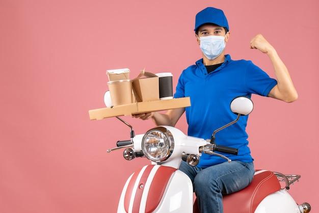 Вид спереди гордого доставщика-мужчины в маске в шляпе, сидящего на скутере, доставляющего заказы, показывая его мускулистость на пастельном персиковом фоне
