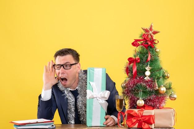 크리스마스 트리 근처 테이블에 앉아 뭔가를 듣고 엿보는 남자의 전면보기와 노란색 선물