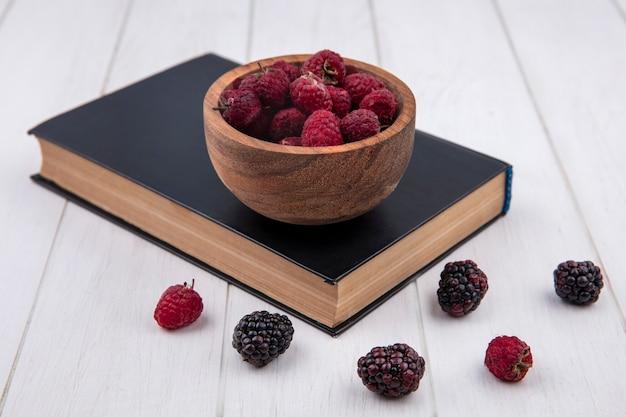 Вид спереди малины в миске на книге с ежевикой на белой поверхности