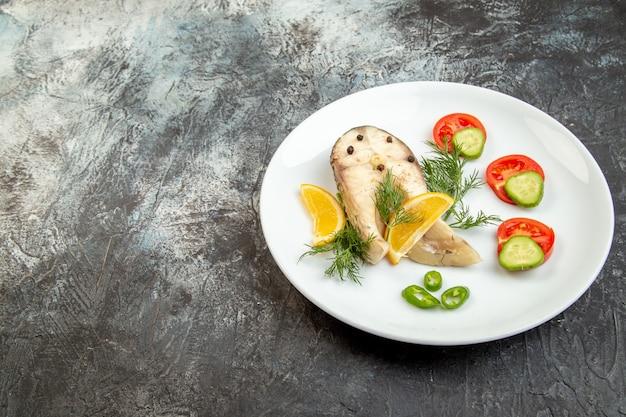 여유 공간이있는 회색 얼음 표면의 왼쪽에 흰색 접시에 생선과 고추 신선한 음식의 전면보기
