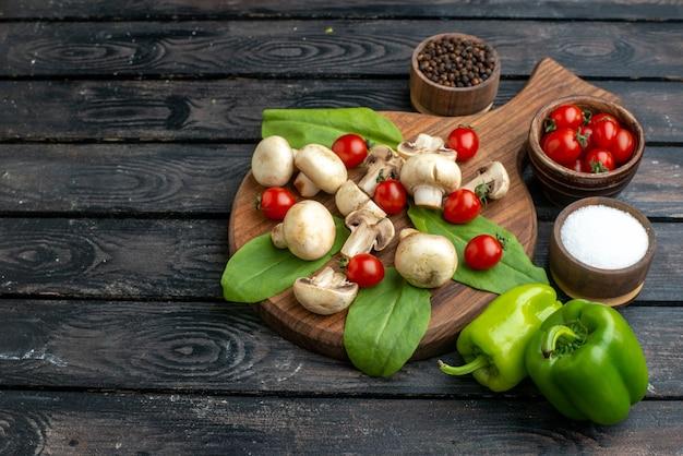 검은색 바탕에 나무 판자에 있는 신선한 생 버섯과 토마토 향신료의 전면 전망